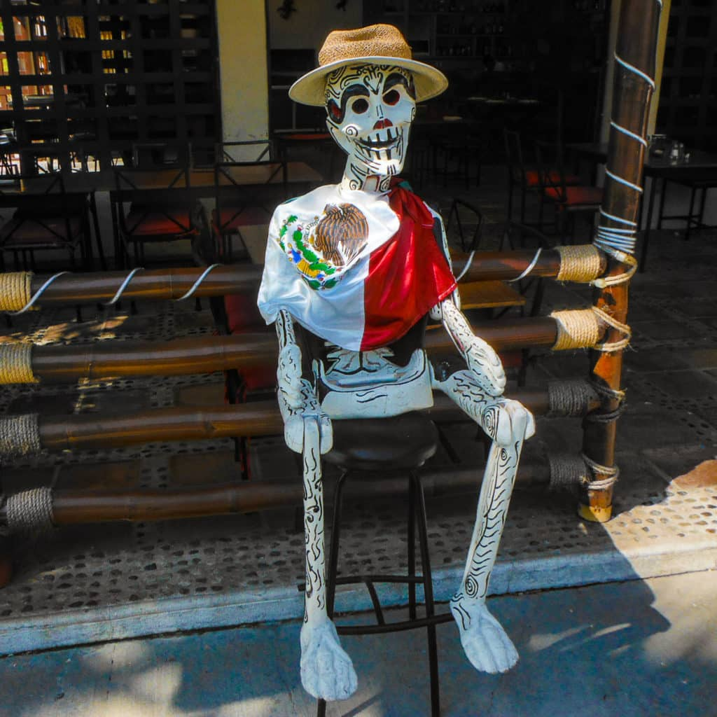 """Mexican painted """"Day of the Dead"""" skeleton sitting on stool outside of bar in Huatulco, Mexico"""
