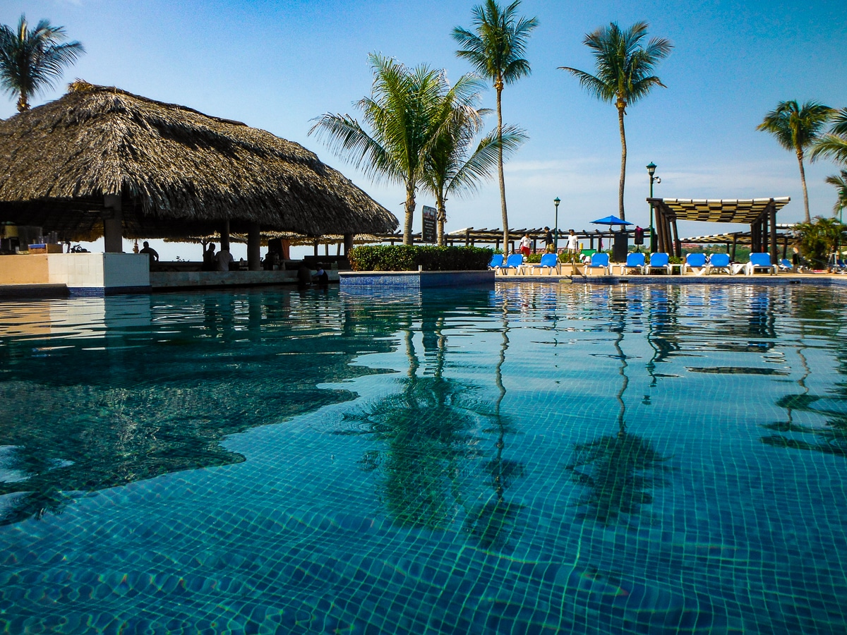 Swimming pool and bar overlooking beach at Barcelo Huatulco resort in Mexico