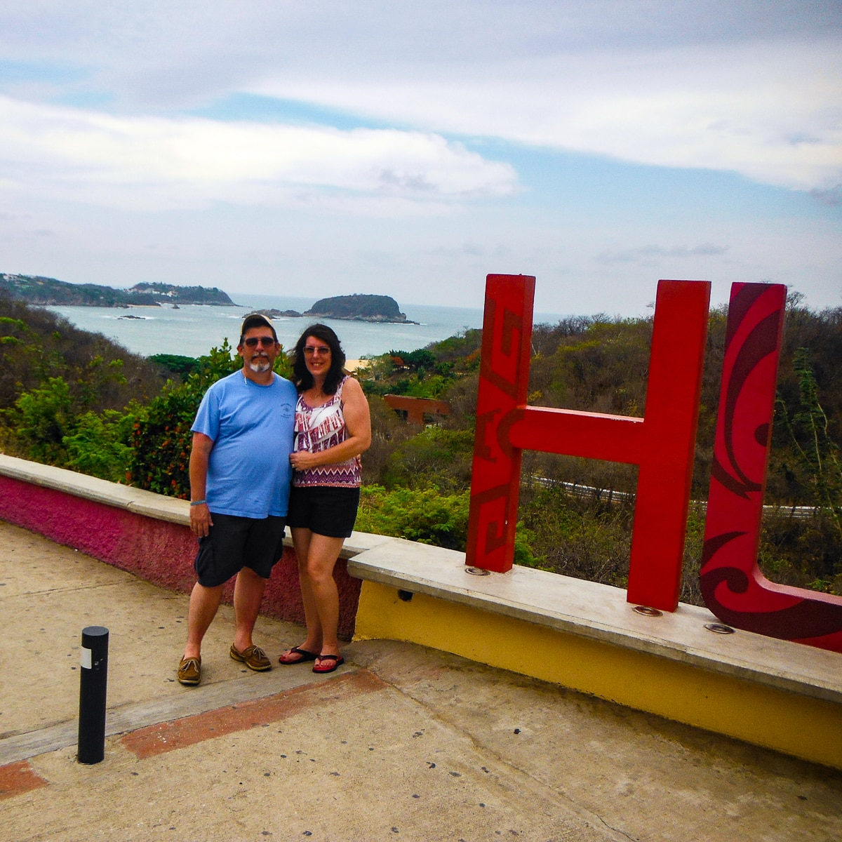 Charlie and Lynn standing next to Huatulco, Mexico sign with Pacific Ocean in backround.