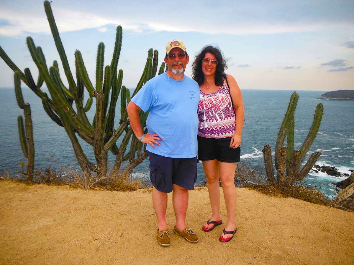 Charlie and Lynn standing on cliff with cactus overlooking Pacific Ocean in Huatulco, Mexico