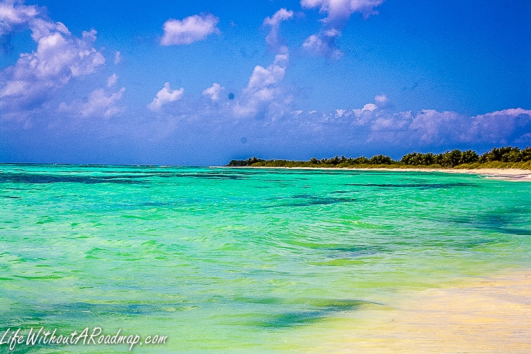 Sand and turquoise waters of Caribbean sea with deep blue sky