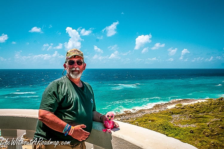 Charlie standing at top of lighthouse overlooking island and deep blue Caribbean sea
