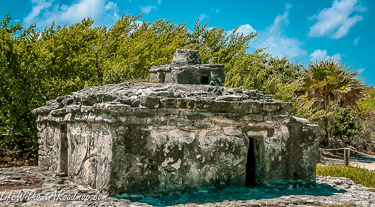 Ancient Myan ruin with trees in background in Cozumel, Mexico